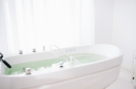 Modern hydro massage bathtub placed next to the window in a spa salon without people in it Stok Fotoğraf