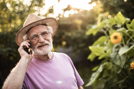 Old male person smiling while having telephone conversation in spring garden. Copy space on right side