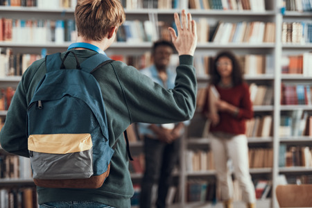 Young man in casual clothes and with backpack waving his hand while coming to the library and noticing fellow students