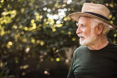 Waist up portrait of elderly bearded man in hat standing in garden and looking away. Copy space in left side 스톡 콘텐츠