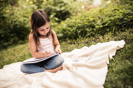 Pretty child in casuale clothes writing something in notebook while sitting on lawn. Copy space on right side