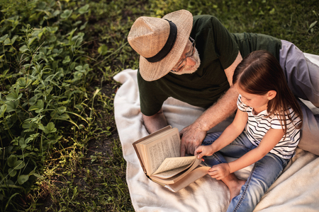 Top view of little girl with her grandparent spending time in fresh air and reading stories 스톡 콘텐츠 - 114089423