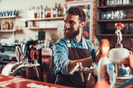 Serving best beer in city. Waist up portrait of handsome bearded man pouring alcoholic drink while standing at bar counter. He is looking away and smiling Stok Fotoğraf