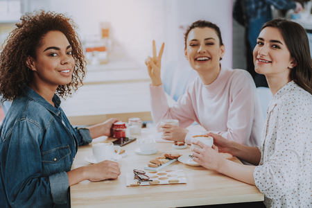 Positive young female friends sitting in the cafe while enjoying time together