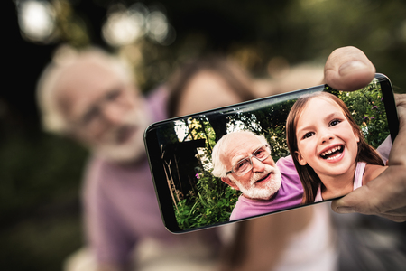 Senior gray-haired man in glasses with funny laughing girl shooting themselves on smartphone while sitting in summer garden. Focus on phone screen Archivio Fotografico