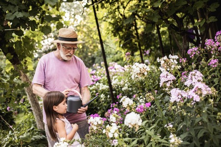 Serious mature man in linen wide brimmed hat standing with his granddaughter standing near flower bed and holding watering can 写真素材