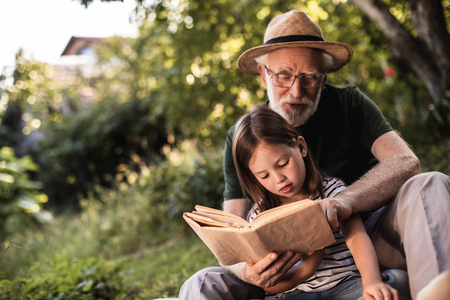 Mature bearded man in glasses and straw hat showing something in open book his preteen grandchild while they are sitting on grass 写真素材