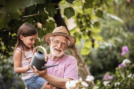 Glückliche kleine Enkelin mit ihrem lächelnden Großvater, der in der Nähe von Blumen steht und eine Gießkanne hält