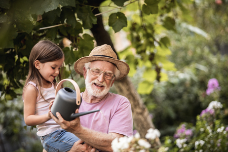 Happy little graddaughter with her smiling grandfather standing near flowers and holding watering can