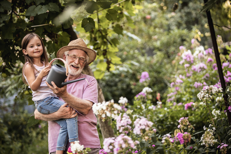 Mature man in flaxen hat holding his little grandchild while she watering flowers in garden