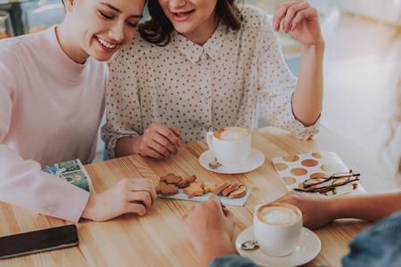 Cheerful nice female friends resting in the cafe while enjoying freshly baked cookies Stock Photo