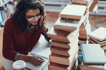 Positive pretty young lady making notes and smiling while sitting at the table with a pile of books in front of her