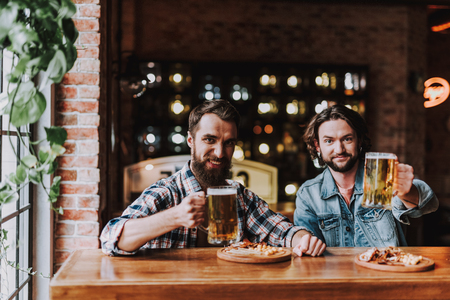 Portrait of two friends holding mugs of lager beer while looking at camera and smiling