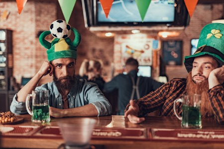 No more drinks today. Two men in green hats spending time at pub while celebrating Saint Patrick Day