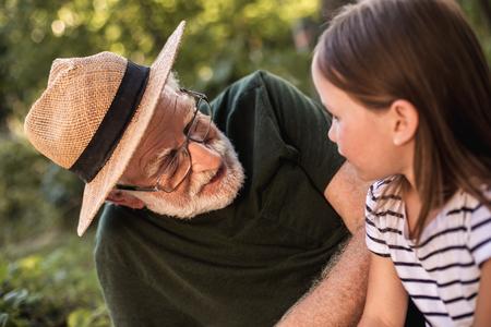 Senior gray-haired man telling something her female grandchild while sitting in garden 스톡 콘텐츠 - 114702050