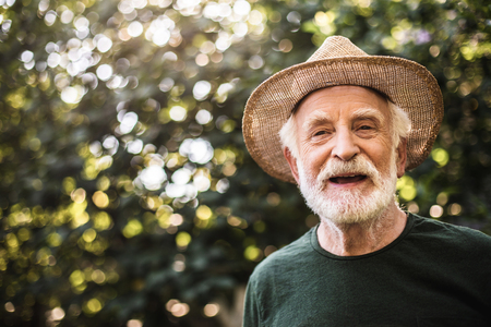 Waist up portrait of smiling senior man with gray beard standing in stylish linen hat on blurred foliage background. Copy space on left side 스톡 콘텐츠 - 114703935