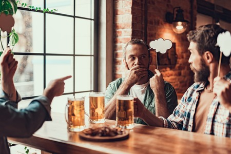 Young man covering mouth with hand while bearded gentleman looking at him with serious expression. They sitting at the table with drinks and snacks
