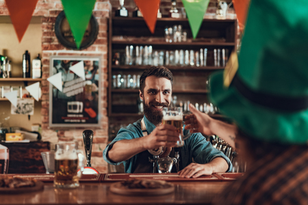 Delicious beverage for you. Handsome bearded bartender standing at bar counter and serving drink to man in green hat. He is looking at client and smiling