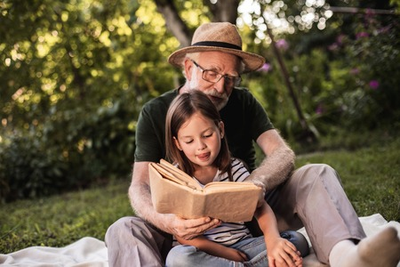 Grandfather and cute girl sitting on lawn on picnic blanket and read book