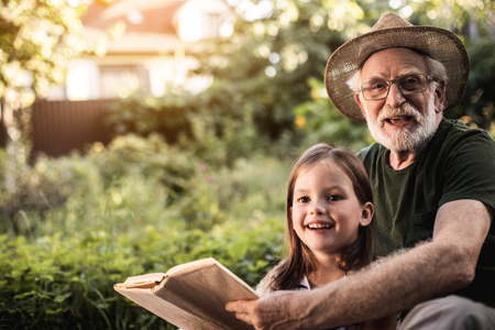 Happy smiling girl reading book with her grandfather in garden of country house. Copy space in left side