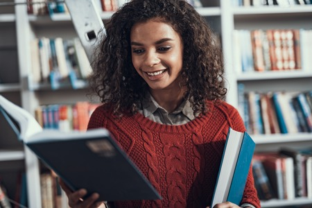 Curious student feeling interested and smiling while being in the library and taking a book