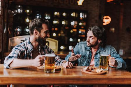 Ich sage dir. Seitenansichtporträt von gutaussehenden bärtigen Männern, die kommunizieren, während sie am Tisch sitzen und Bierkrüge halten