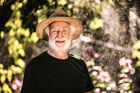 Smiling senior man in straw hat standing against a blooming garden