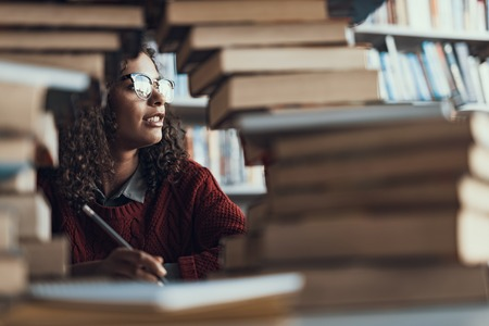 Thoughtful curly lady sitting in the library with a pile of books and looking into the distance while holding a pencil