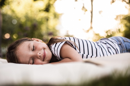 Satisfied little girl with eyes closed lying on white rug in daylight with foliage on background