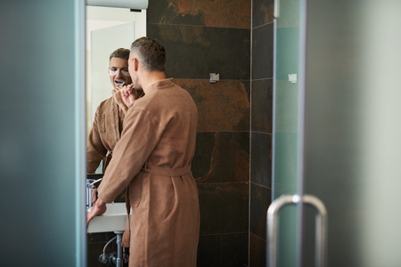 Back view portrait of attractive gentleman with masks under lower eyelids looking in the mirror while cleaning teeth with toothbrush. He is wearing bathrobe Stock Photo
