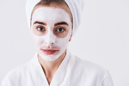 Close up portrait of beautiful woman in bathrobe looking at camera and smiling slightly while having skin care procedure