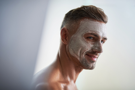 Close up portrait of handsome gentleman having skincare cosmetic procedure. He is looking away and smiling