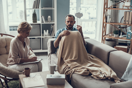 Serious bearded man resting on the sofa under the blanket and frowning while putting thought cloud to his head and psychotherapist making notes