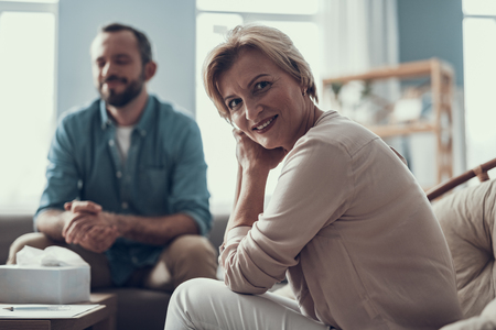 Selective focus of positive friendly psychotherapist sitting not far from her client and smiling happily