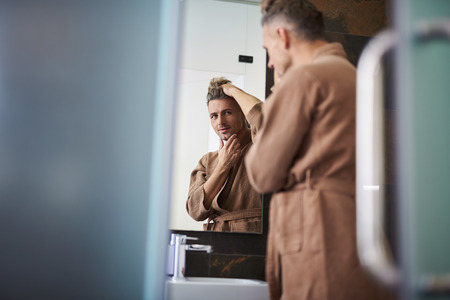 Handsome unshaven gentleman in bathrobe fixing his hair while touching chin and smiling slightly