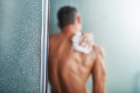 Back view of muscular naked gentleman taking shower at home. Focus on doorway