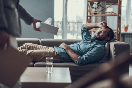 Depressed middle aged man looking attentively at his psychotherapist offering him a box of napkins while lying on the sofa