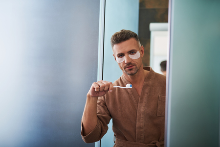 Skincare and hygiene. Waist up portrait of handsome unshaved gentleman in bathrobe holding toothbrush with toothpaste. Copy space in left side