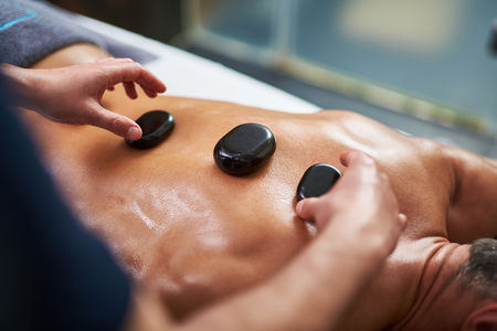 Top view close up picture of young man lying on massage table and receiving therapeutic spa procedure Foto de archivo