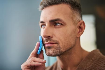 Nettoyer la peau. Close up portrait of attractive gentleman non rasé essuyant le visage avec une éponge cosmétique