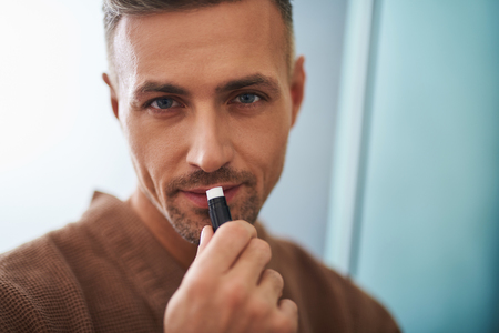 Beauty and health. Close up portrait of attractive unshaven gentleman applying balm on lips 写真素材