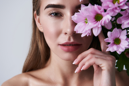 Close up portrait of charming lady with lovely bouquet looking at camera with slightly opened mouth