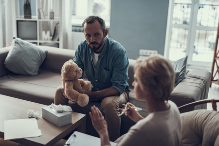 Serious curious man sitting on the sofa with teddy bear and looking attentively at his psychotherapist talking and gesturing