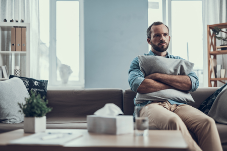 Serious middle aged man sitting on the sofa with a pillow in his hands and frowning while looking into the distance 版權商用圖片