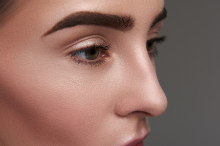 Close up of beautiful female eyes with long lashes and brown eyebrows with perfect shape Фото со стока