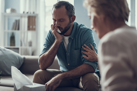 Thoughtful man sitting with his eyes closed and pressing tissue to the face while his professional psychotherapist touching his shoulder and sitting near