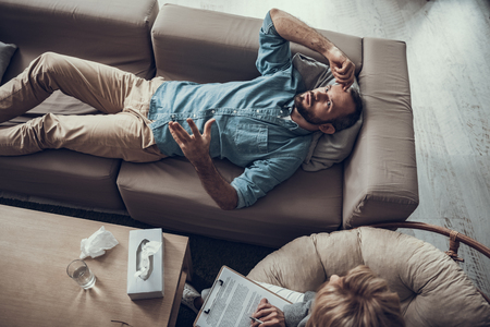 Serious middle aged man lying on the sofa and putting hand up while gesturing during his conversation with psychotherapist