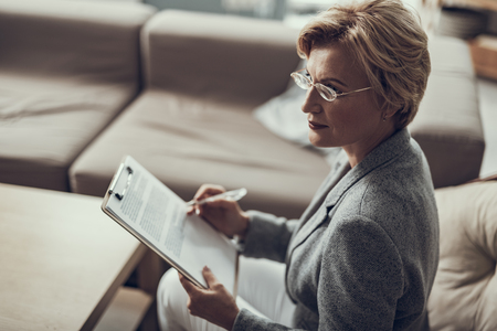 Calm experienced middle aged psychologist wearing glasses and looking away while holding clipboard with notes