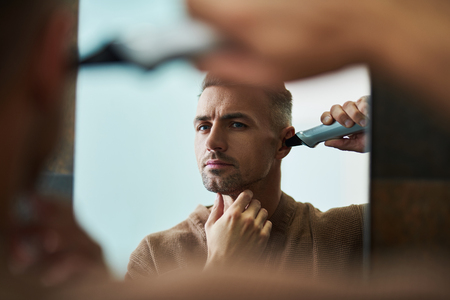 Portrait of good-looking gentleman in bathrobe using electric trimmer while looking in the mirror with serious expression Stok Fotoğraf