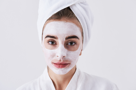 Close up portrait of beautiful young woman with towel on her head having skin care procedure. She is looking at camera and smiling slightly